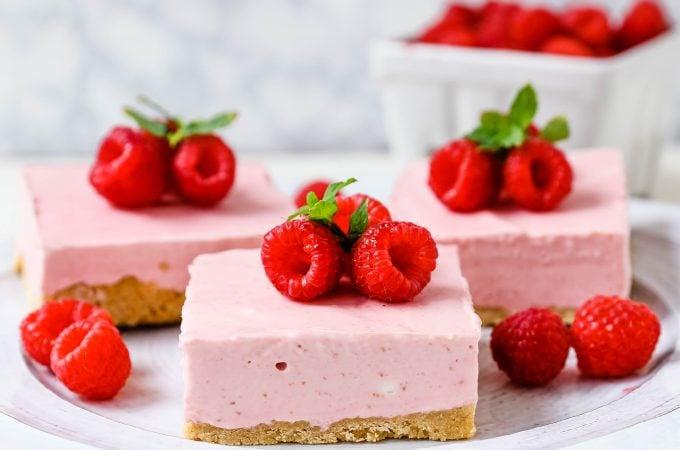 No-Bake Frozen Raspberry Cheesecake Squares. Creamy no-bake raspberry cheesecake filling on top of a shortbread or graham cracker crust topped with fresh raspberries. A creamy no-bake frozen dessert. www.modernhoney.com #nobakedessert #raspberrycheesecake #cheesecakesquares #frozendessert #frozencheesecake