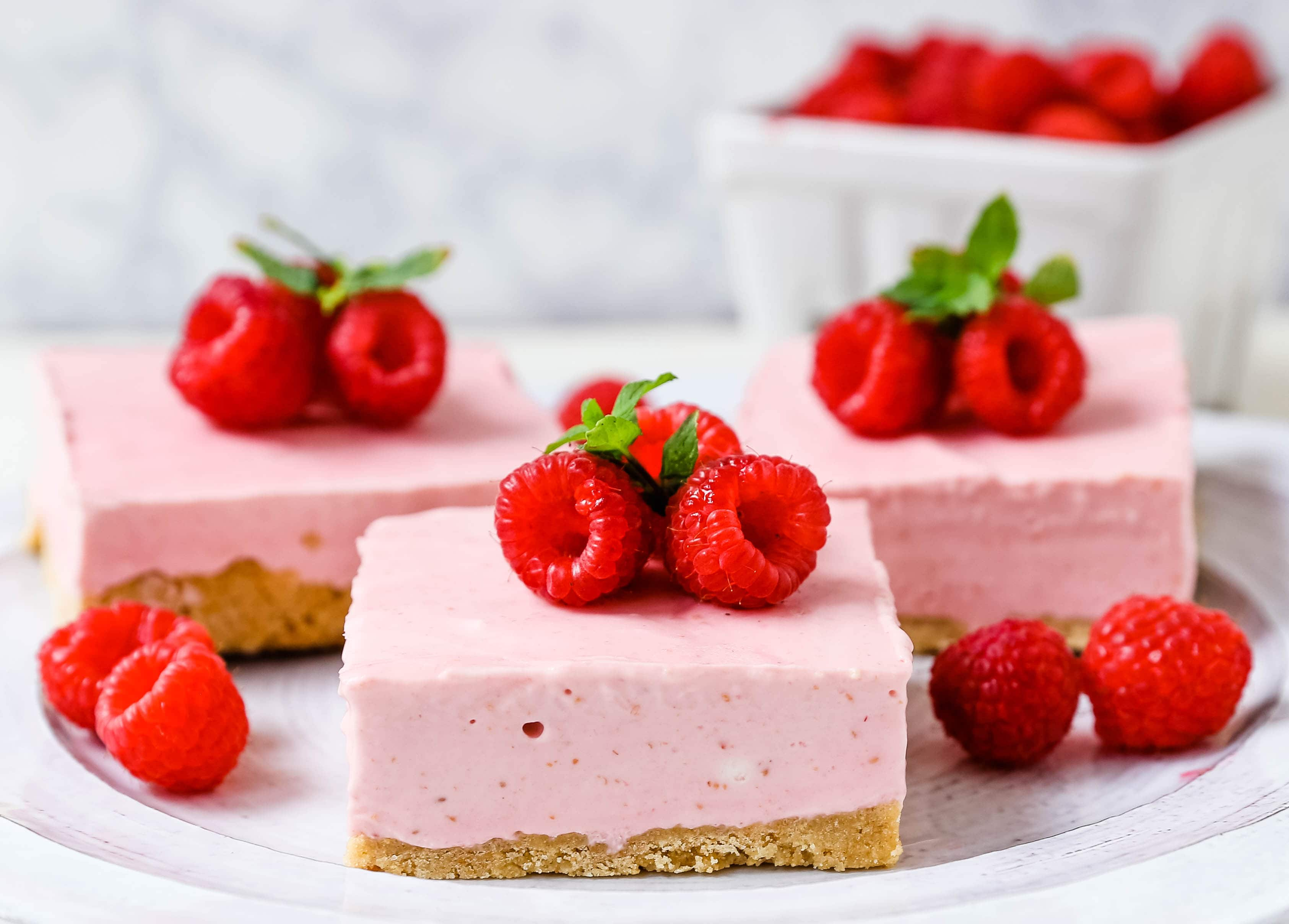 No-Bake Frozen Raspberry Cheesecake Squares. Creamy no-bake raspberry cheesecake filling on top of a shortbread or graham cracker crust topped with fresh raspberries. A creamy no-bake frozen dessert.  www.modernhoney.com #nobakedessert #raspberrycheesecake #cheesecakesquares #frozendessert #frozencheesecake
