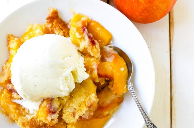 Peach Dump Cake The easiest 4-ingredient peach dessert. Fresh peaches, a touch of sugar, French vanilla cake mix, and butter all baked until golden and topped with vanilla ice cream. The simplest peach cobbler dessert recipe! www.modernhoney.com #peach #peaches #peachdesserts #peachcobbler #peachdumpcake