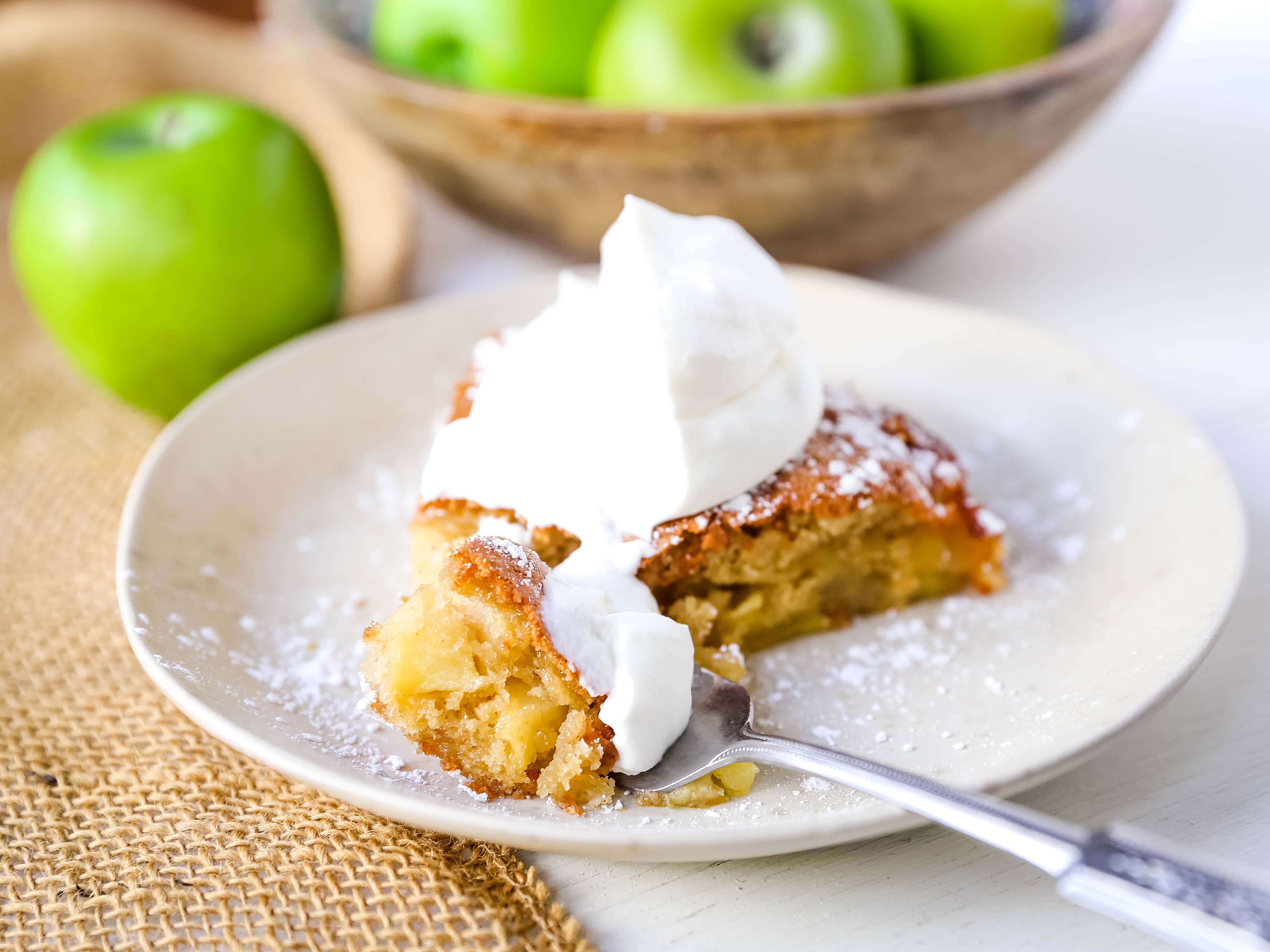 French Apple Cake A simple French buttery cake made with sweet apples and topped with freshly whipped cream. www.modernhoney.com #frenchapplecake #applecake #frenchcake #dessert #appledessert