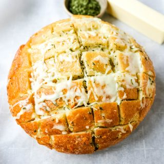 Cheesy Pull-Apart Garlic Bread Warm sourdough bread baked with garlic butter, melted mozzarella cheese, and spices. The best pull-apart garlic cheese bread! www.modernhoney.com #garlicbread #cheesebread #garliccheesebread