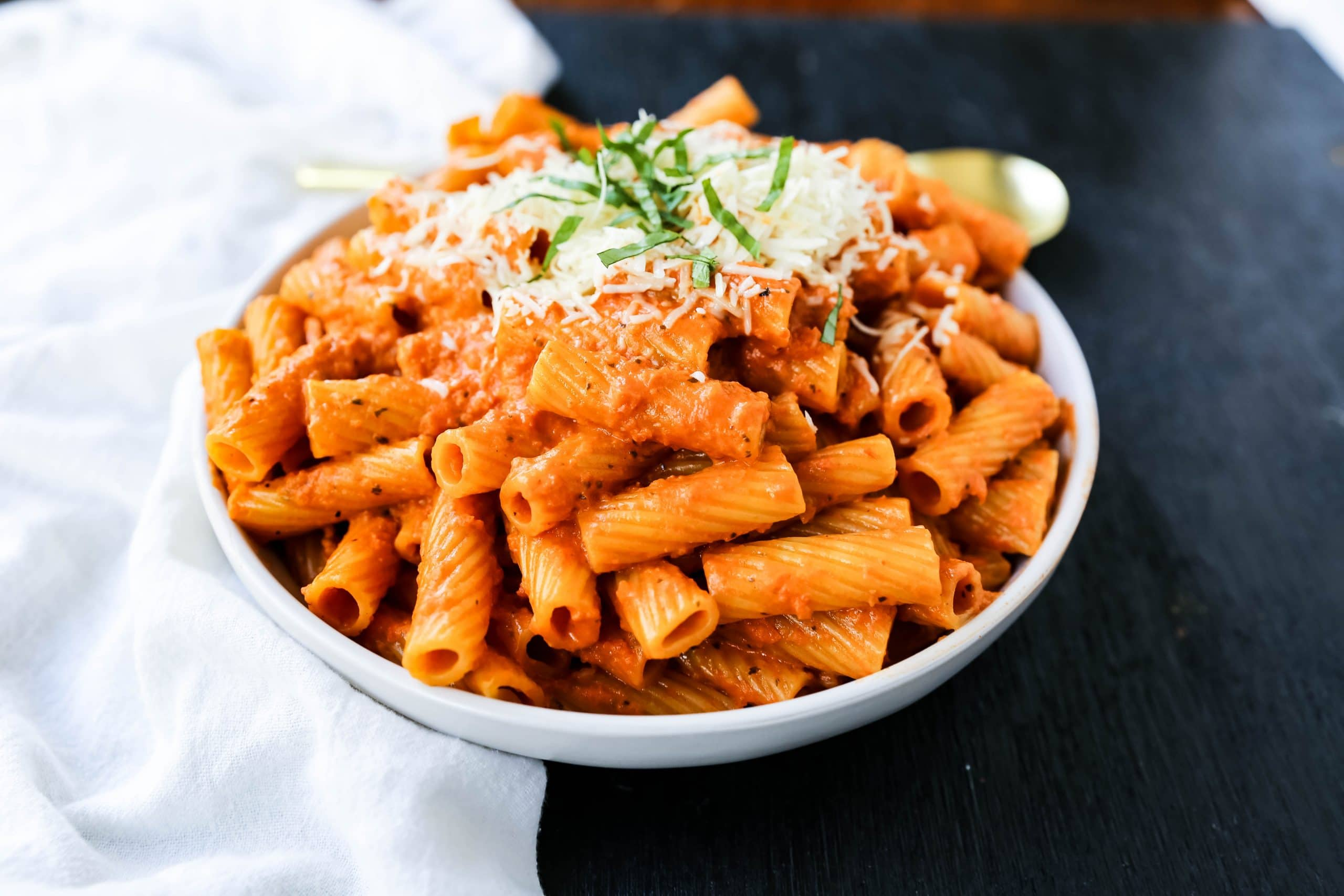 Creamy Roasted Red Pepper Pasta  A creamy roasted red pepper and tomato basil sauce with garlic and heavy cream all tossed together with pasta and topped with parmesan cheese. A flavorful robust pasta dish! www.modernhoney.com #pasta #italian #italianfood