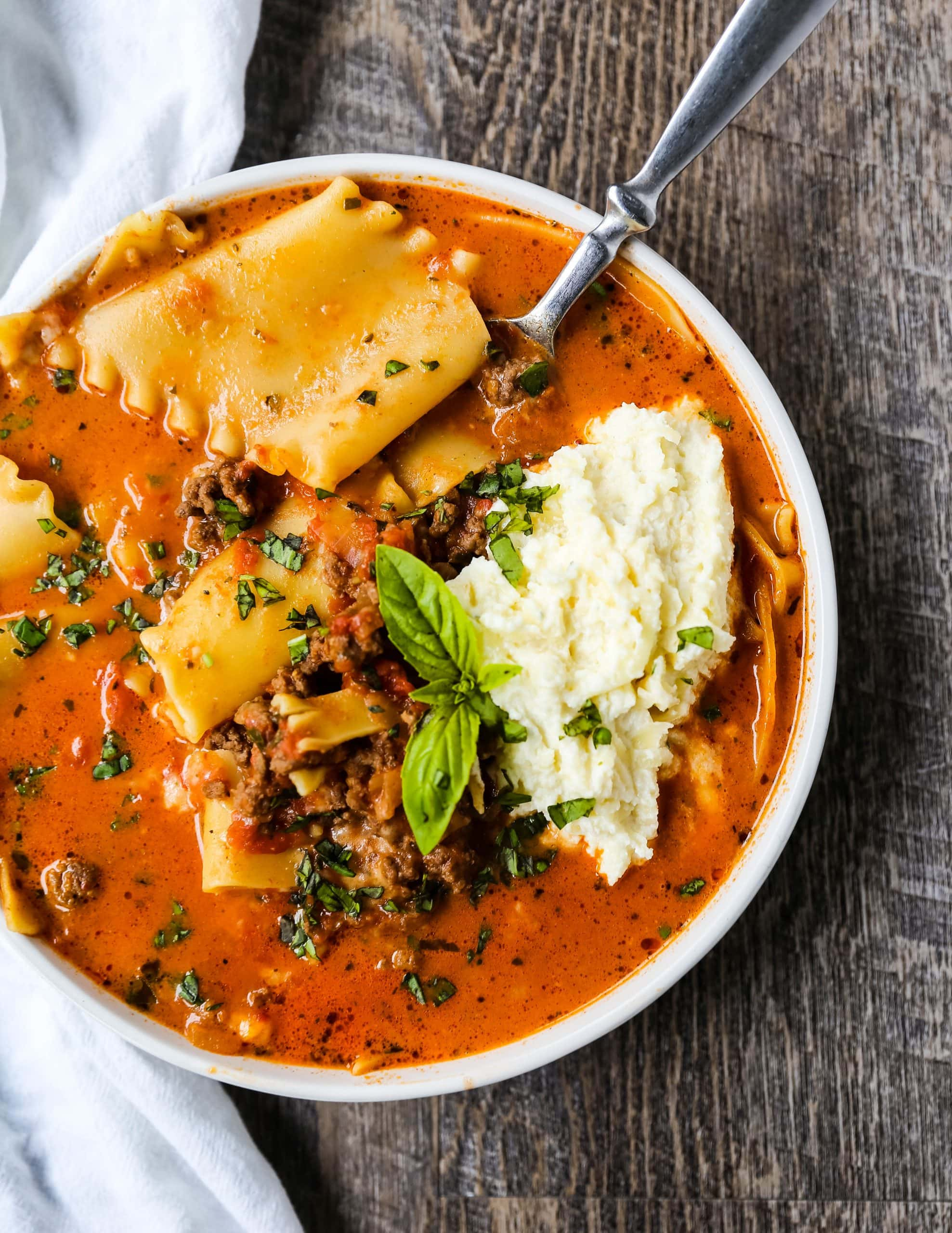 Lasagna Soup. A hearty beef lasagna soup with fresh ricotta cheese, mozzarella, and parmesan cheeses and fresh herbs. An Italian classic made into a comforting soup! #lasagnasoup #soup #soups #comfortfood
