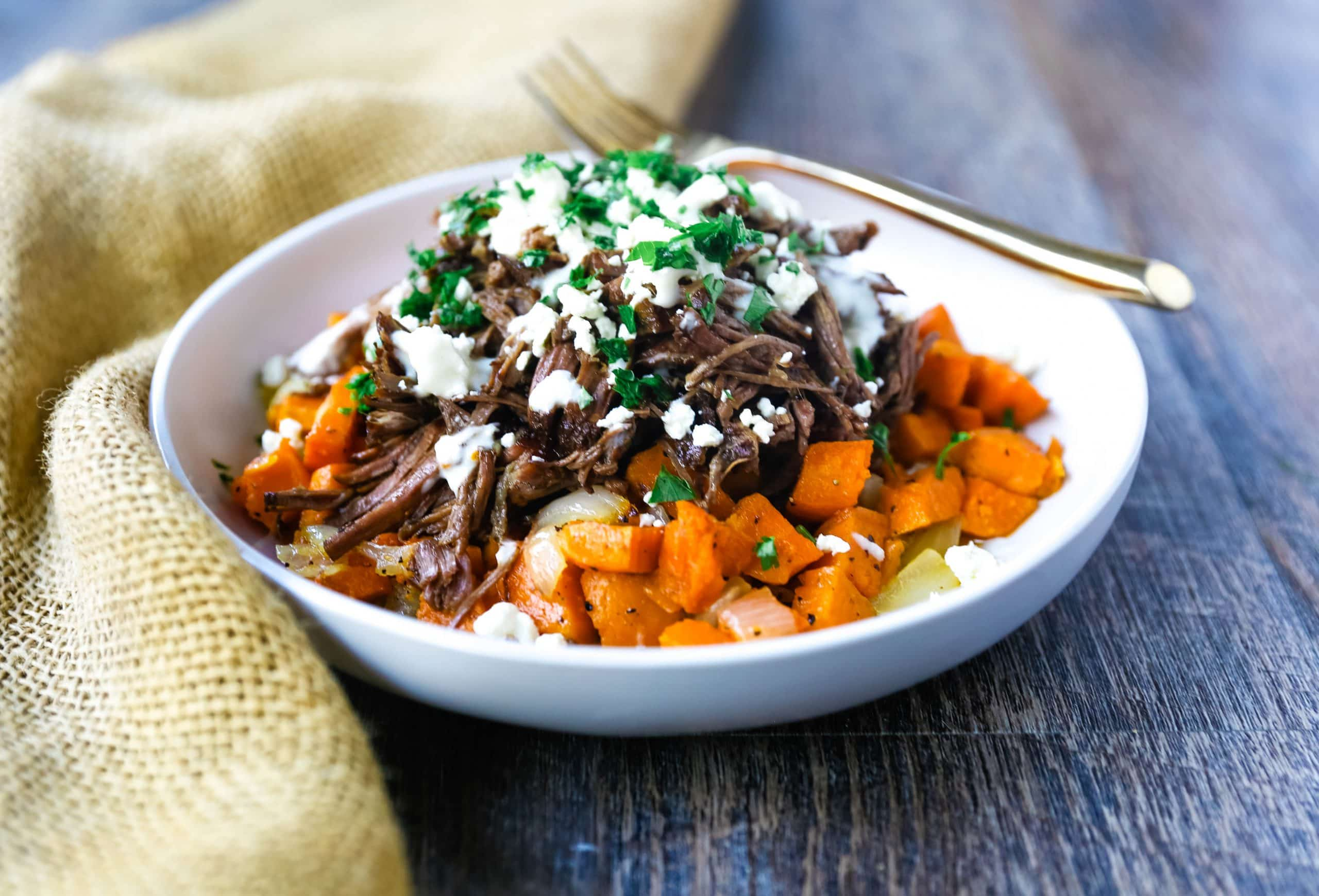 Braised Beef and Sweet Potato Hash Bowl. Tender braised beef on top of a sweet potato onion hash and topped with feta cheese and herbs. www.modernhoney.com #bowl #bowls #dinner