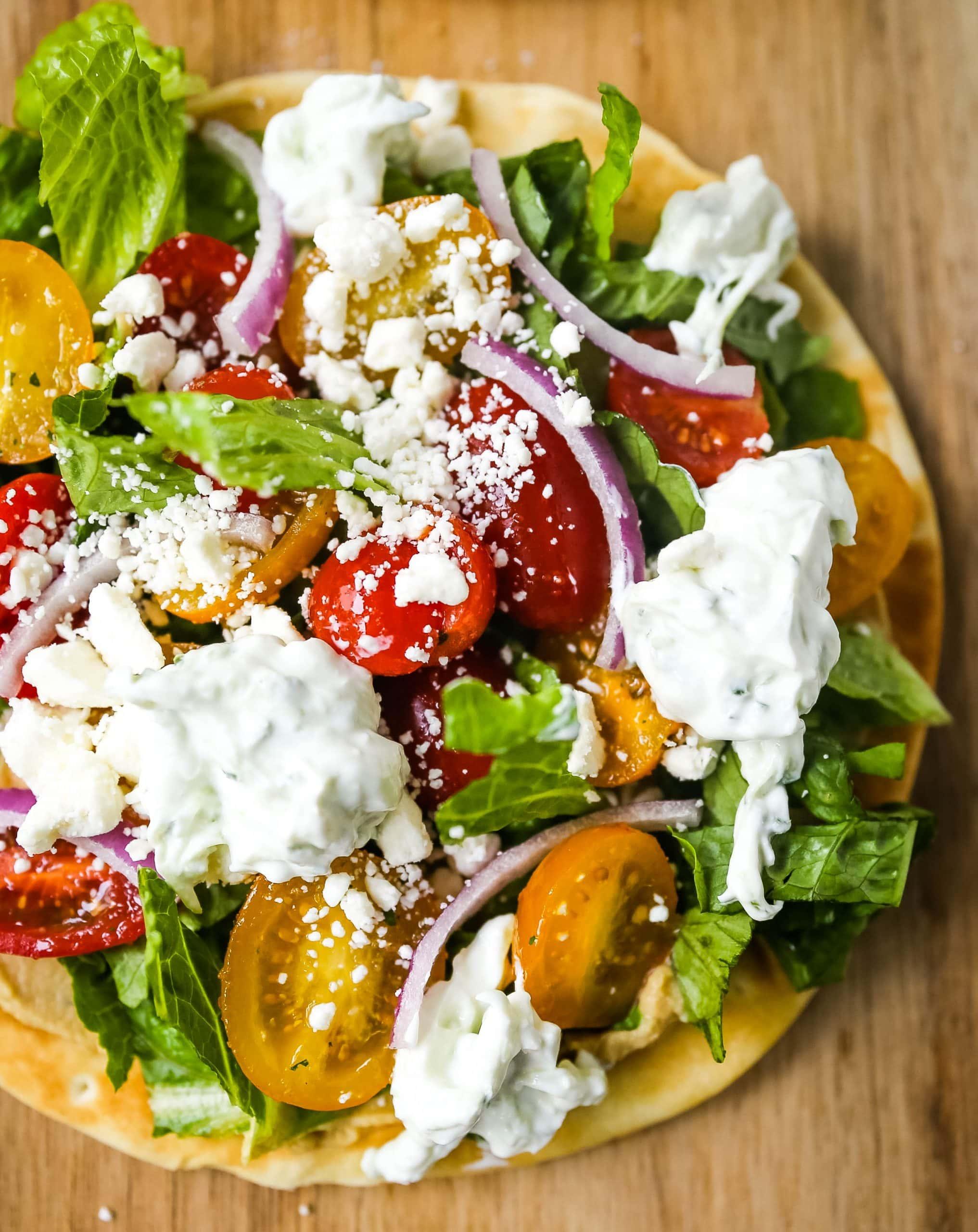 Greek Salad Pita Pizzas Soft pita bread topped with creamy hummus, romaine lettuce, juicy grape tomatoes, feta cheese, red onion, cucumber, and a homemade fresh tzatziki sauce.www.modernhoney.com #greek #greekfood #salad #pita