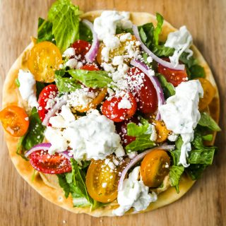 Greek Salad Pita Pizzas Soft pita bread topped with creamy hummus, romaine lettuce, juicy grape tomatoes, feta cheese, red onion, cucumber, and a homemade fresh tzatziki sauce. www.modernhoney.com #greek #greekfood #salad #pita