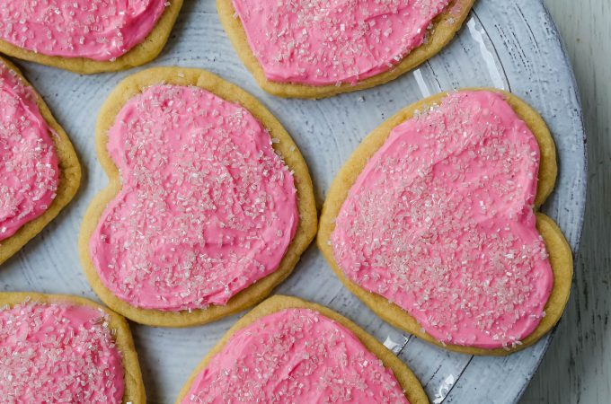 Jacque's Buttery Sugar Cookies. Homemade buttery sugar cookies with sweet buttercream frosting. The perfect frosted sugar cookie recipe! www.modernhoney.com #sugarcookies #buttercookies #buttersugarcookies #heartcookies #valentinesday #valentinesdaycookies