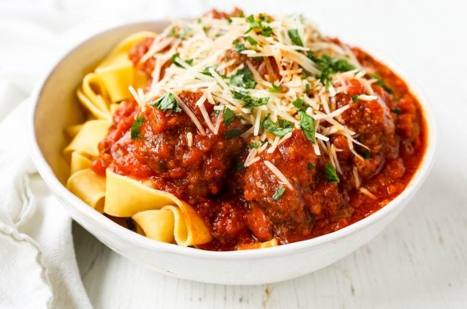Slow Cooker Meatballs. Tender, moist homemade meatballs made with ground beef, sausage, parmesan cheese, bread crumbs, and spices. Slow cooking the meatballs make the most melt-in-your-mouth meatball! www.modernhoney.com #meatball #meatballs #italian #italianfood #pasta