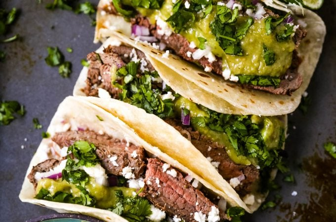 Grilled Steak Tacos. Juicy marinated grilled steak tacos with fresh cilantro, avocado, and salsa. The most flavorful and tender steak tacos recipe! www.modernhoney.com #tacos #steaktacos #steak #beeftacos