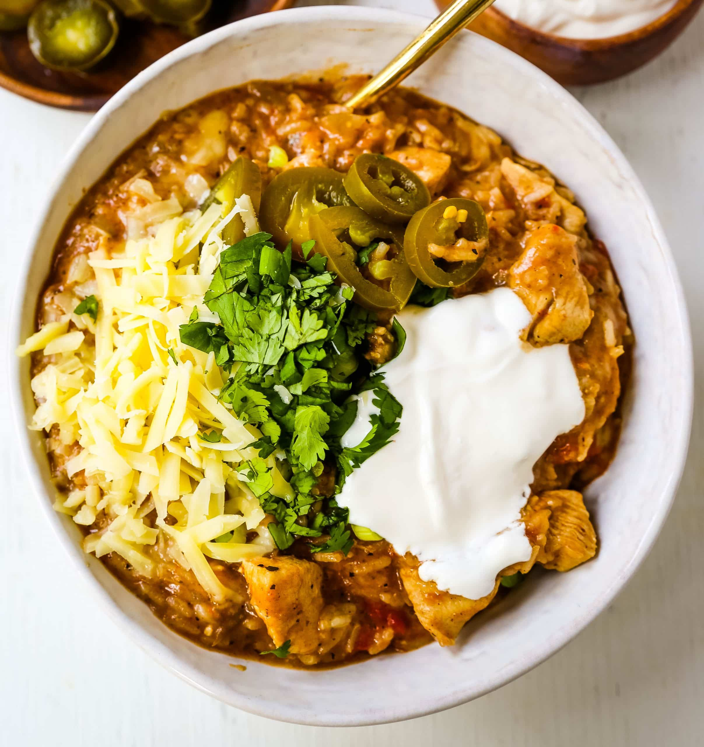 Cheesy Mexican Chicken and Rice Skillet Mexican chicken with green chilies, tomatoes, Mexican spices, rice, and cheese. An easy 30-minute dinner recipe! www.modernhoney.com #skilletdinner #30minutemeal #30minutedinner #mexicanfood #mexican