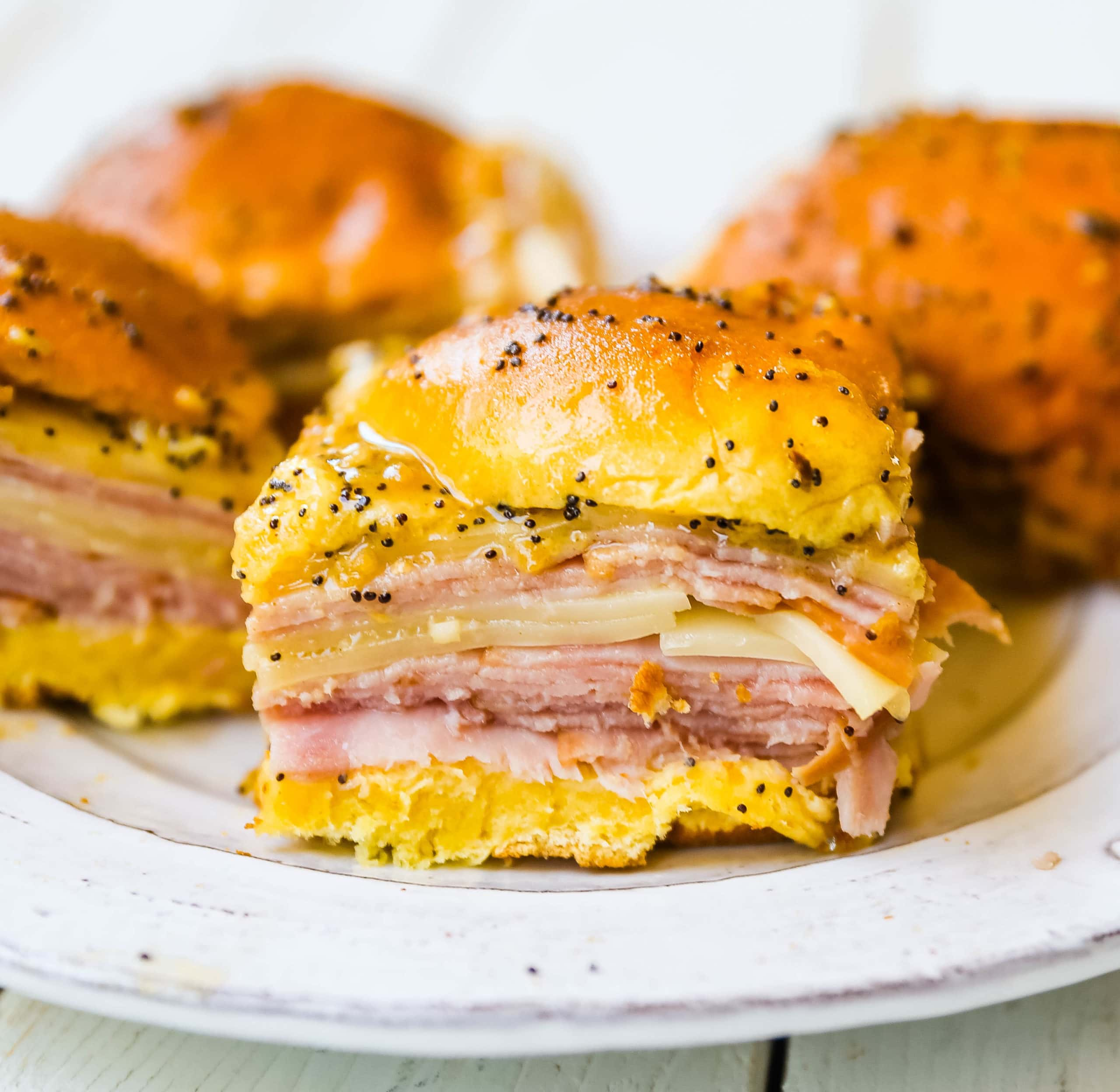 Ham and Cheese Sliders  These baked ham and cheese sliders and layered with ham, melted cheese, on a Hawaiian sweet roll, and basted with a flavorful, buttery sauce. www.modernhoney.com #sandwiches #sliders #hamandcheesesliders