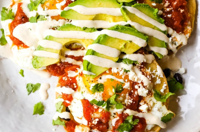 Huevos Rancheros. A traditional Mexican breakfast dish made with fried corn tortillas, fried egg, ranchera salsa, beans, avocado, cheese, and salsa.  #huevosrancheros #mexican #mexicanfood #breakfast