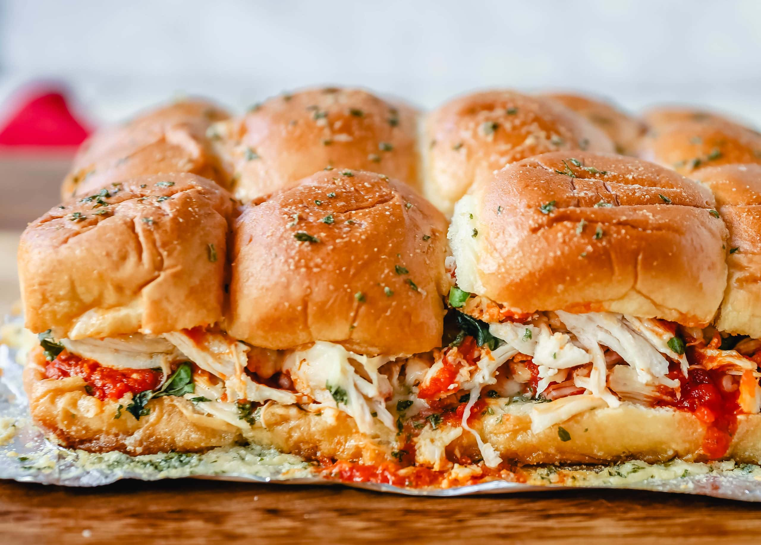 Baked Chicken Parm Sliders Chicken topped with a fresh marinara sauce topped with fresh mozzarella cheese and baked on Hawaiian sweet rolls and slathered with garlic butter. www.modernhoney.com #italian