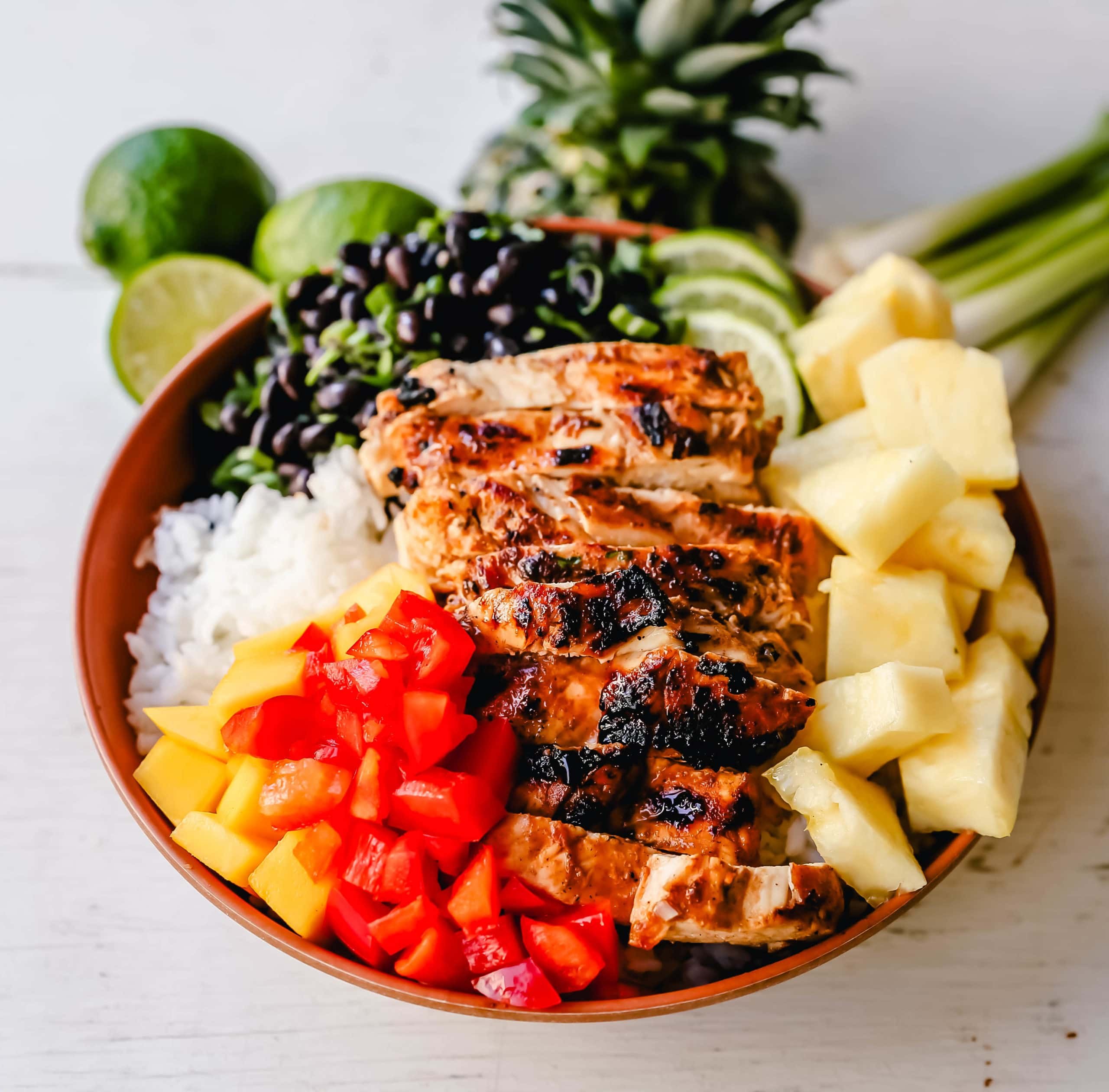 Jerk Chicken Bowl Jamaican spiced grilled Jerk Chicken with rice, black beans, cilantro, fresh pineapple and mango, and red peppers. www.modernhoney.com #jerkchicken #chicken #chickenbowl