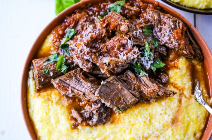 Italian Braised Beef Ragu with Parmesan Polenta Slow-cooked braised beef in a hearty homemade Italian tomato garlic sauce on top of creamy parmesan polenta. A true comfort food! www.modernhoney.com #ragu #italian #italianfood #polenta #beef #slowcooker