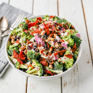 Broccoli Salad. Crunchy broccoli salad with crispy bacon, sweet dried cranberries, onion, nuts, tossed in a sweet and tangy dressing. A classic potluck side dish recipe! www.modernhoney.com #broccolisalad #sidedish #potluck #sides