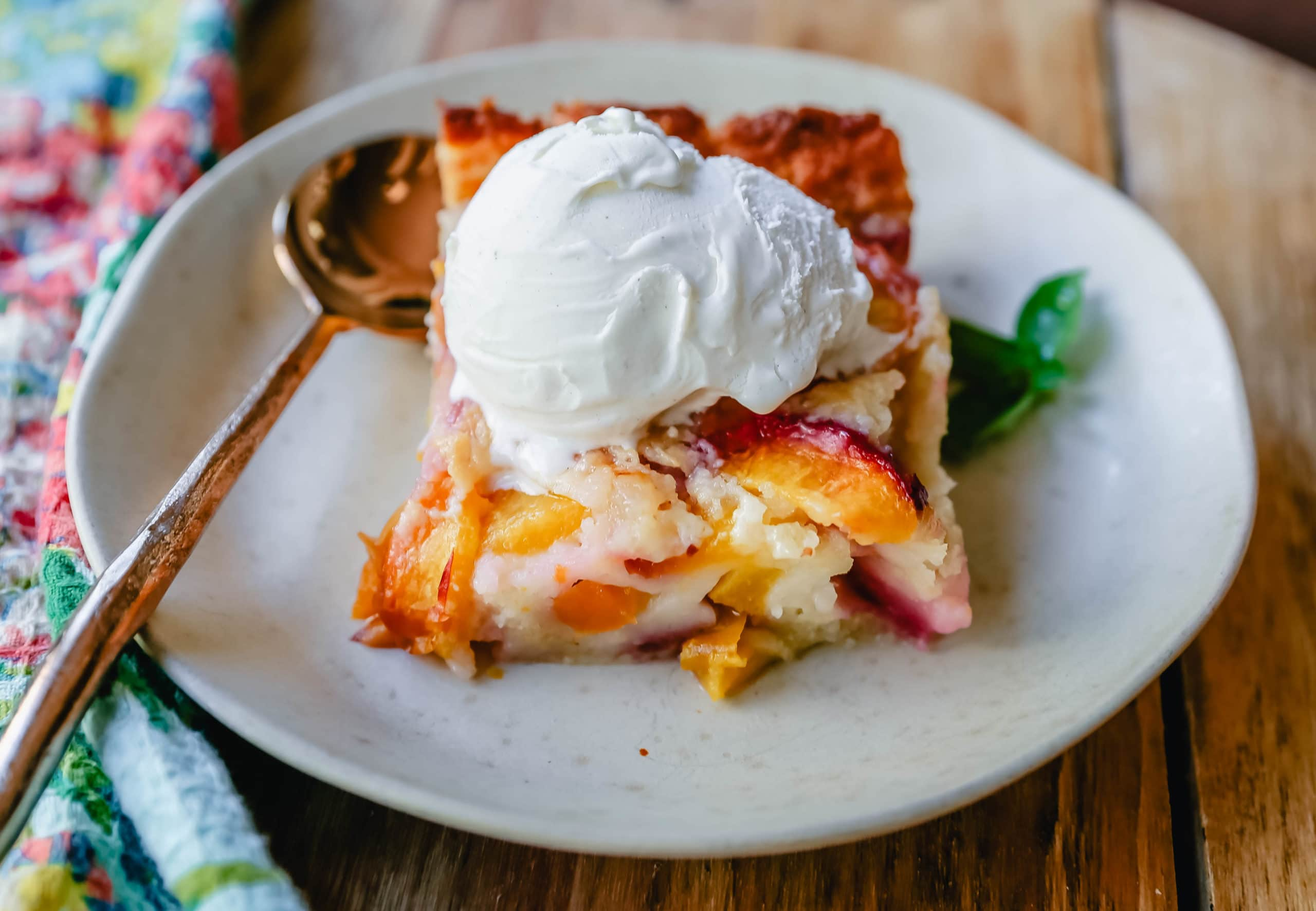 Texas Style Peach Cobbler. Fresh peaches sweetened with sugar and topped with a creamy buttery cake-like topping. A Texas favorite dessert! #peaches #peachdessert #peachcobbler