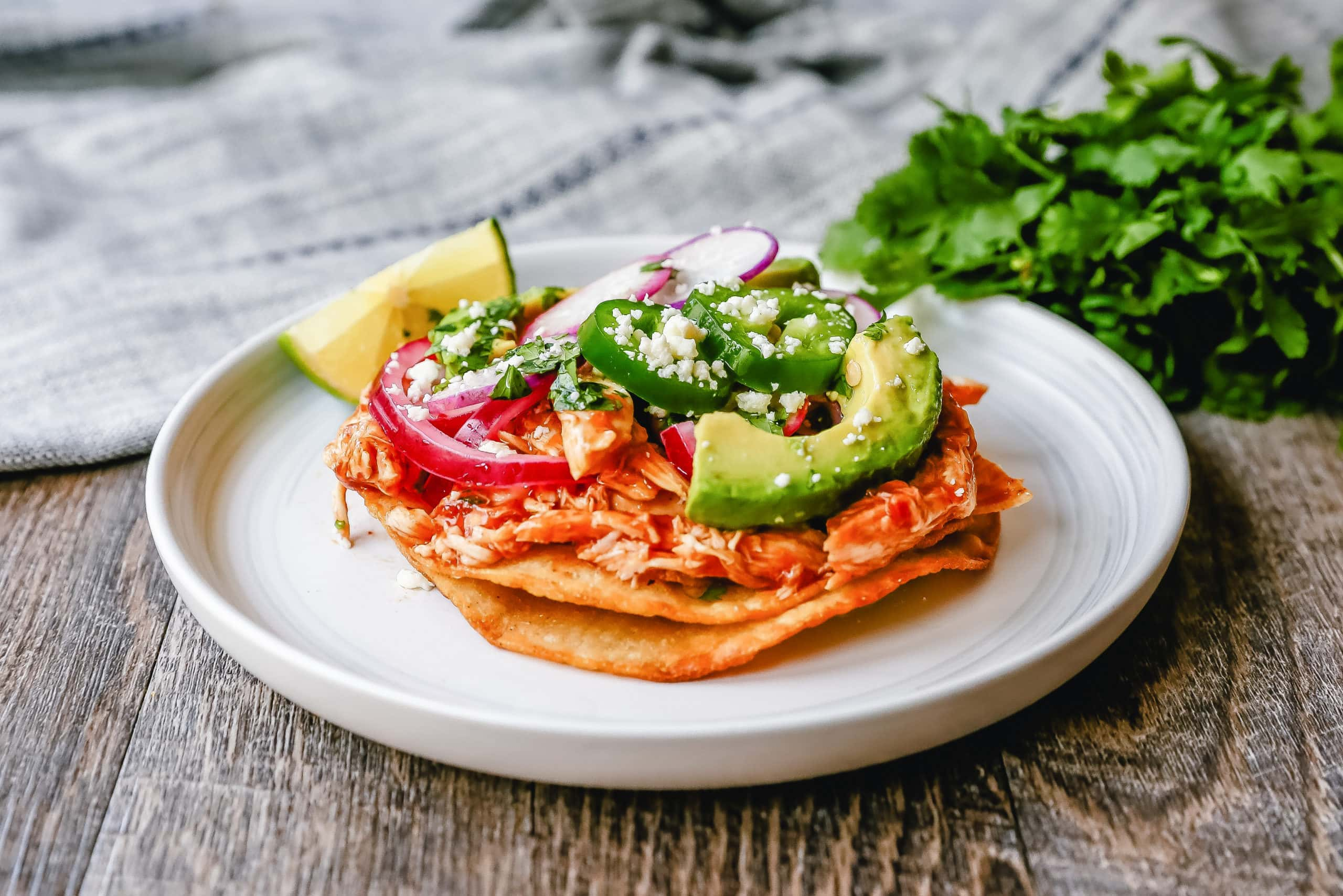 Chicken Tostadas Chile Chicken Tostadas made with homemade tostada shells topped with chile spiced chicken topped with cotija cheese, cilantro, pickled red onion, fresh avocado, and jalapeños.