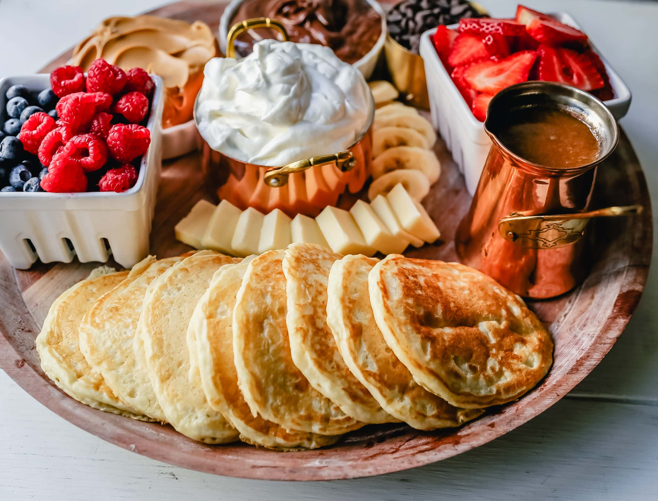 Breakfast Pancake Board. The perfect breakfast for entertaining! Homemade buttermilk pancakes topped with all of your favorite toppings -- fresh berries, whipped cream, homemade syrup, Nutella, chocolate chips, peanut butter, and more.